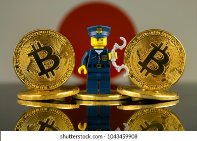 WROCLAW, POLAND - MARCH 10, 2018: Physical version of Bitcoin, Police Officer (as Lego figure) and Japan Flag. Studio shot.