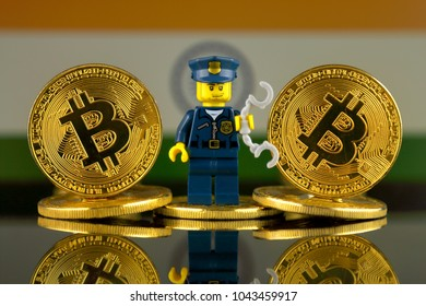 WROCLAW, POLAND - MARCH 10, 2018: Physical version of Bitcoin, Police Officer (as Lego figure) and India Flag. Studio shot.