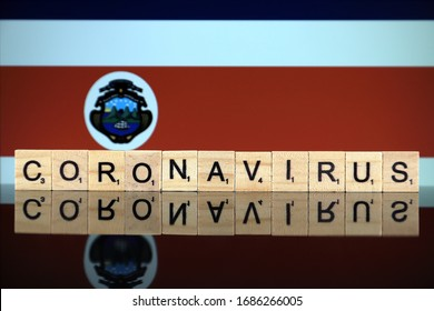 WROCLAW, POLAND - MARCH 28, 2020: Word CORONAVIRUS made of wooden letters, and Costa Rica Flag in the background. Coronavirus (COVID-19) global disease 2020.
