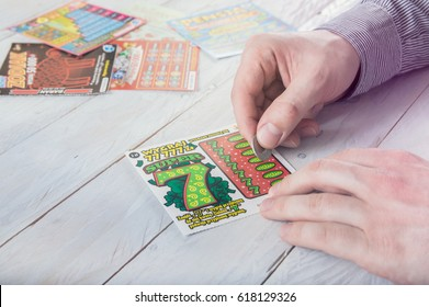 WROCLAW, POLAND -  MARCH 28th, 2017: Man scratches Polish lottery scratchcard. Scratchcard is a small card, where areas contain concealed information which can be revealed by scratching off.