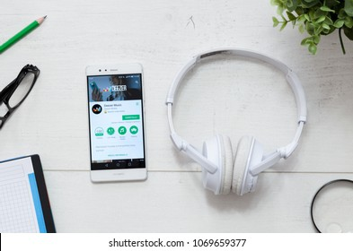WROCLAW, POLAND - MARCH 29, 2018: Deezer is a service that offers legal streaming music. Smartphone with Deezer app in Google Play store on desk concept.