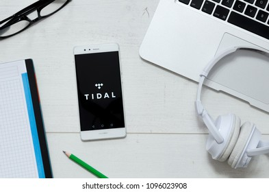 WROCLAW, POLAND - MARCH 29, 2018: Tidal is a music service that offers legal streaming music. Smartphone with Tidal app logo on desk concept.