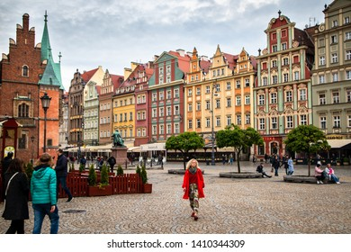 Wroclaw / Poland - may 09 2019: Town Hall building on Wroclaw central market square (rynek) in Wroclaw old historic town with old colourful buildings and tourists at evening