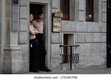 Wroclaw, Poland - May 18, 2020: Two waiters are standing near the service entrance to the restaurant on the first day of the opening of restaurants after quarantine