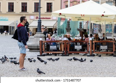 Wroclaw, Poland - May 18, 2020: A young man speaks on the phone in the Market Square where many pigeons sit
