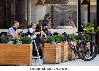 Wroclaw, Poland - May 18, 2020: Restaurant visitors sit at tables outside on Market Square on the first day restaurants open after quarantine