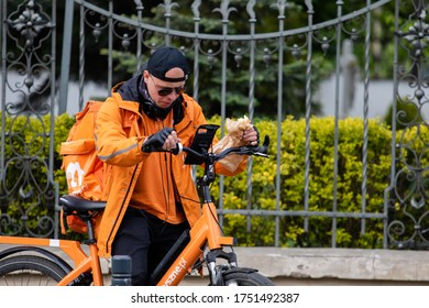 Wroclaw, Poland - May 18, 2020: Young male courier in orange uniform eats on the go, delivering an order to a customer