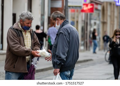 Wroclaw, Poland - May 18, 2020: A masked man passes a bag on the street to another man