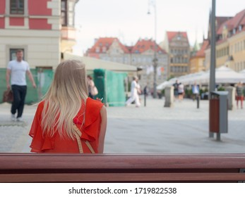 Wroclaw / Poland - May 25th 2012: A woman is waiting and smoking a cigarette, sit on a bench in the streets of Wroclaw in Poland during summertime.