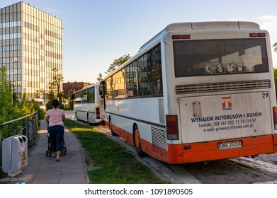 Wroclaw, Poland - May 5, 2018: Woman with baby buggy on a sidewalk passing a parked dirty travel bus in the city