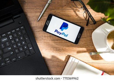 WROCLAW, POLAND - NOVEMBER 17th, 2017: Samsung A5 is laying on the desk with PayPal logo on screen. PayPal Holdings, Inc. is an American company operating a worldwide online payments system