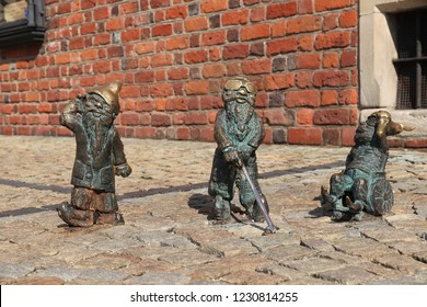 WROCLAW, POLAND - SEPTEMBER 2, 2018: Disabled gnomes or dwarves bronze statuette in Wroclaw, Poland. Wroclaw has 350 gnome sculptures around the city.