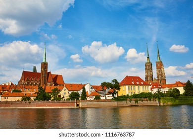 Wroclaw Poland view at Tumski island and Cathedral of St John the Baptist with bridge through river Odra. Landscape blue sky white cloud.