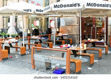 Wroclaw, Republic of Poland - May 19, 2019: Early Sunday morning. Garbage and leavings in the street tables of McDonald's restaurant in the central square of the city.