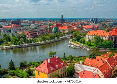 Wroclaw/Poland- August 18, 2017: aerial panoramic cityscape – river Odra, part view of Tumski Island,  historical and modern buildings, alley, park and green trees summertime, blue sky