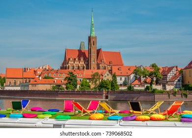 Wroclaw/Poland- August 18, 2017: View of Church of Holy Cross and St. Bartholomew on Tumski Island and Odra river through touristic boat deck with colorful chairs and pillows for sunbathing