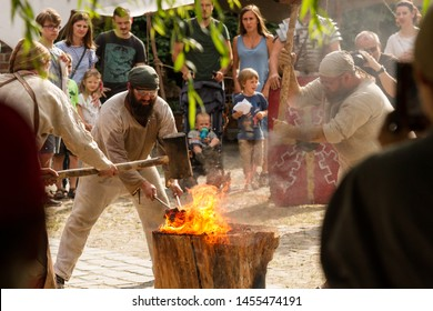 """WROCLAW/POLAND - JUNE 16 2019: """"People of Fire"""" (PL: """"Ludzie Ognia"""") event. Educational show of archaic   methods and art crafts concern fire. People smelt steel in an ancient clay furnace"""