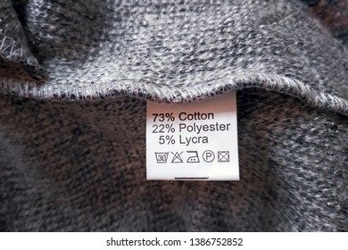 Wrong side of a gray dress made of wool, the composition is specified: cotton, polyester and lycra. Fabric composition clothes label on gray texture background.