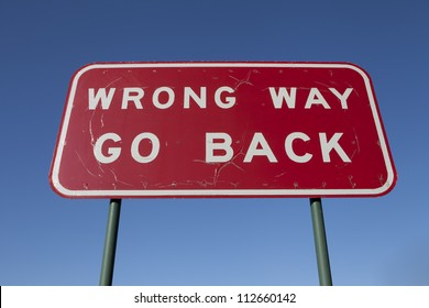 Wrong way go back road sign.