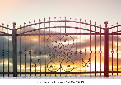 wrought iron fence and sunset sky in background