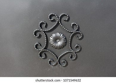 Wrought iron gate flower like custom made ornament on dark grey metal plate