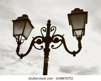 Wrought iron lamp posts with a  white cloudy sky as background.