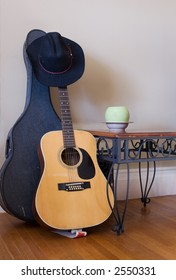 Wrought iron table, modern planter, old wood floors and textured walls with guitar and guitar case.