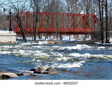 Wrought iron truss bridge, river view, winter scene