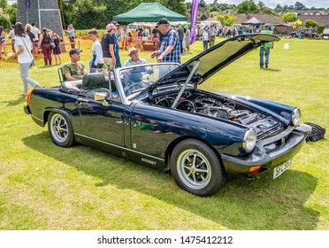 Wroxham, Norfolk, UK – July 21 2019. Side view of a classic MG Midget sports car, in black, with its bonnet up on display at the annual classic car show in Wroxham, Norfolk, UK
