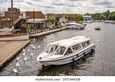 Wroxham, Norfolk, UK – June 01 2019. A large hire boat on the River Bure in the village of Wroxham, Norfolk. In the background is the Hotel Wroxham