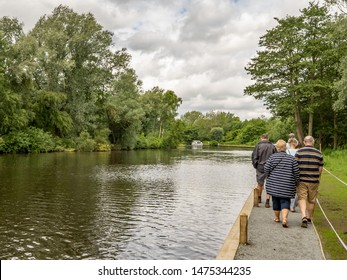 Wroxham, Norfolk, UK – June 01 2019. A group of holiday makers walking back to their hire boat along the bank of the River Bure in the village of Wroxham, Norfolk