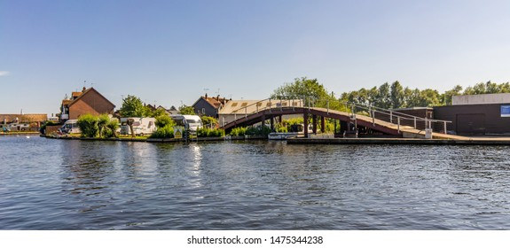 Wroxham, Norfolk, UK – June 01 2019. Small bridge over the river in Wroxham, a small village in the heart of the Norfolk Broads