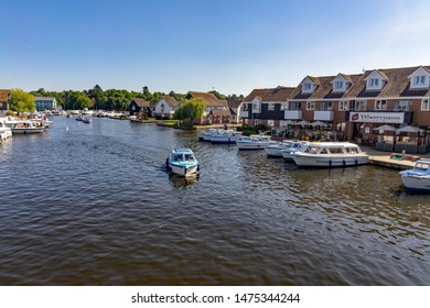 Wroxham, Norfolk, UK – June 01 2019. A small hire boat motoring up the River Bure towards the road bridge in the village of Wroxham, a popular tourist destination in the heart of the Norfolk Broads