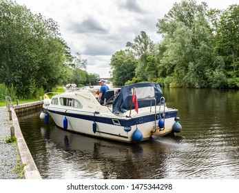 Wroxham, Norfolk, UK – June 01 2019.A middle aged man in a hire boat travelling along the public mooring on the River Bure in the village of Wroxham in Norfolk