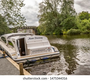 Wroxham, Norfolk, UK – June 01 2019. A pleasure craft holiday boat moored up in the public moorings on the River Bure in the village of Wroxham, Norfolk. In the distance is the rail bridge crossing