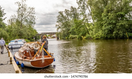 Wroxham, Norfolk, UK – June 16 2019. Traditional wooden sailing boat moored up along the bank of the River Bure in the village of Wroxham, Norfolk. In the distance is the iron railway bridge crossing