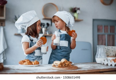 Wth glasses with milk. Family kids in white chef uniform preparing food on the kitchen.