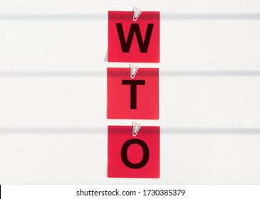 WTO World trade organization acronym message on red paper notes on whie clips on stripes from shadows on whie background