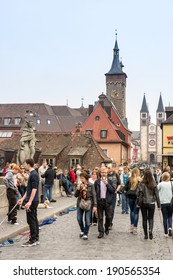 WUERZBURG, GERMANY - APRIL 5: Tourists at the historic Main Bridge of Wuerzburg, Germany on April 5, 2014.  The historic city is over 1300 years old. Foto taken from the bridge.