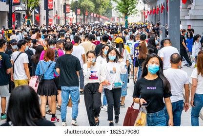 Wuhan China , 1 October 2020 : Crowd of people wearing surgical face mask on the 2020 China national day and first day of golden week holidays in Jianghan pedestrian road in Wuhan Hubei China