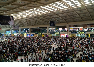 Wuhan, China - July 05 2019: Crowded railway station in China. Huge crowd waiting at railway station. People with baggage waiting for the train in China.