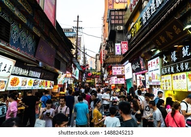 Wuhan, China - July 05 2019: Crowded street full of people looking for something to eat. Crowded alley in Chinese city full of asian people.