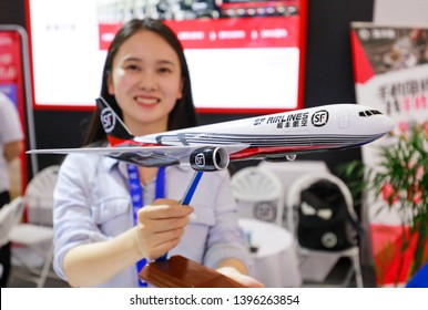 """Wuhan, China - May 10, 2019: a staff member shows a model of an sf express delivery aircraft at the booth of sf express at the China (wuhan) international e-commerce and """"Internet plus"""" industry expo."""