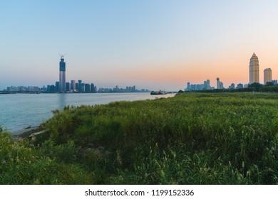 Wuhan riverbank scenery with both Yangtze riverside skyline at sunset in Wuhan Hubei China