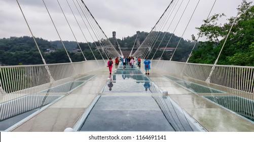 Wulingyuan city, Zhangjiajie Province, China - May 30,2018: Tourists with umbrellas and raincoats at the Glass Bridge Grand Canyon