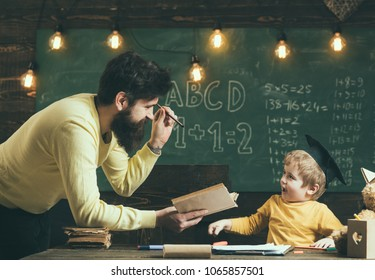 Wunderkind and genius concept. Father, teacher reading book, teaching kid, son, chalkboard on background. Boy child in graduate cap likes to listening dad. Dad wants to grow up genius son.