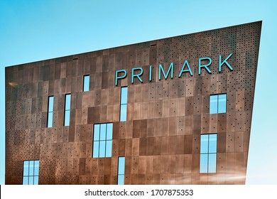 WUPPERTAL, GERMANY - April 17, 2020: Side view of a modern Primark store with a metal facade and large windows. The logo of the company is emblazoned on the building.
