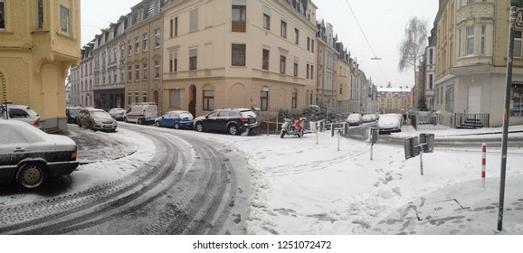 Wuppertal, Germany - December 27th, 2014: Snowed in hilly Street corner with parked cars in Germany