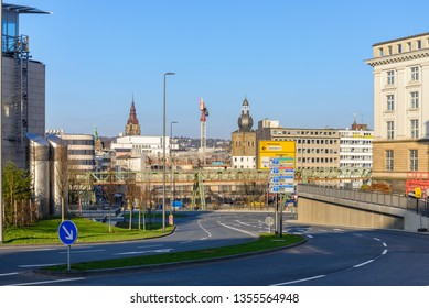 Wuppertal, Germany - February 2019: Outdoor sunny cityscape view of empty street in Wuppertal, Germany, and background of buildings and steel railway structure of Schwebebahn, Suspension Monorail.