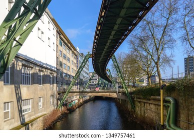 Wuppertal, Germany - March 2019: Outdoor view of Schwebebahn, famous historical landmark Suspension Monorail, carriage hanged from steel rail structure over canal through Wuppertal city, Germany.